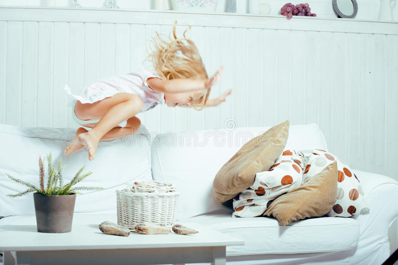 Little cute blonde norwegian girl playing on sofa with pillows, crazy home alone, lifestyle people concept stock photo