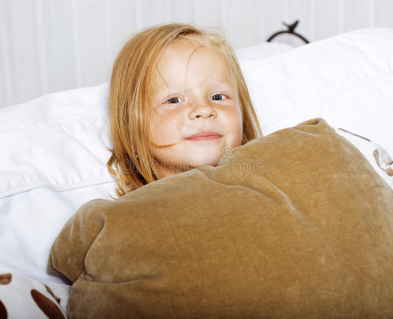 Download Little Cute Blonde Norwegian Girl Playing On Sofa With Pillows, Lifestyle People Concept Stock Photo - Image: 83723076