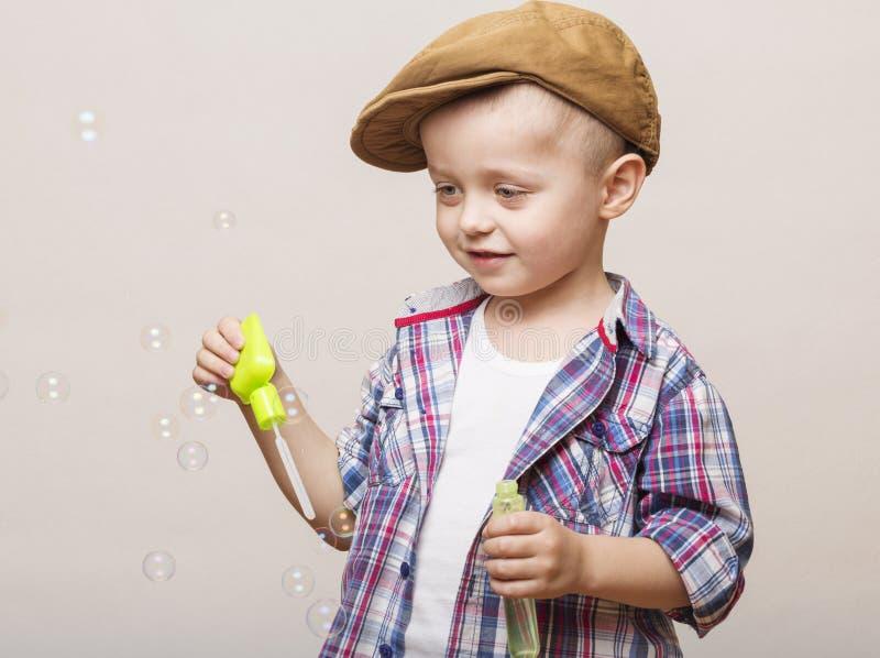 Little cute boy is blowing soap banks stock photo
