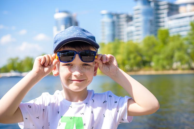 Little cute boy in bright sunglasses shows number one in summer royalty free stock photo