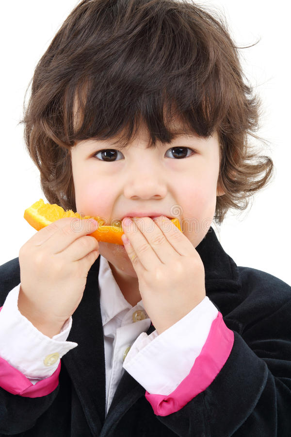 Little cute boy in coat eats orange isolated royalty free stock photos