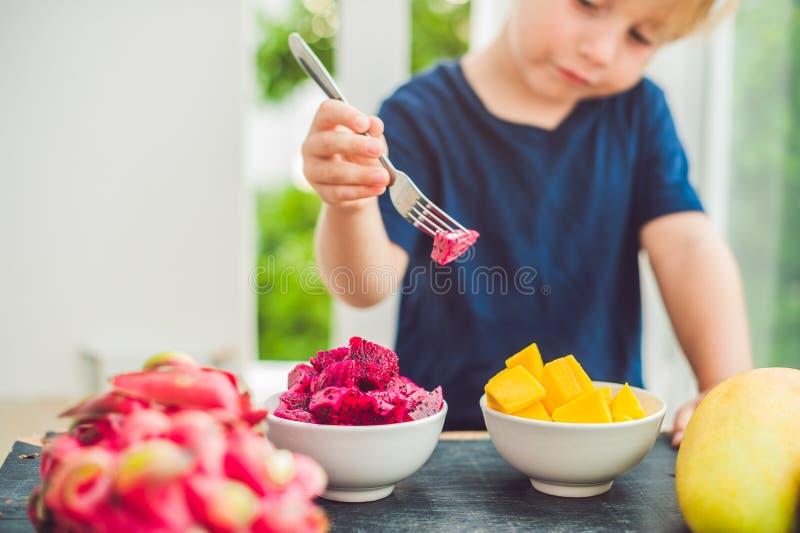 Little cute boy eating mango on the terrace stock photo