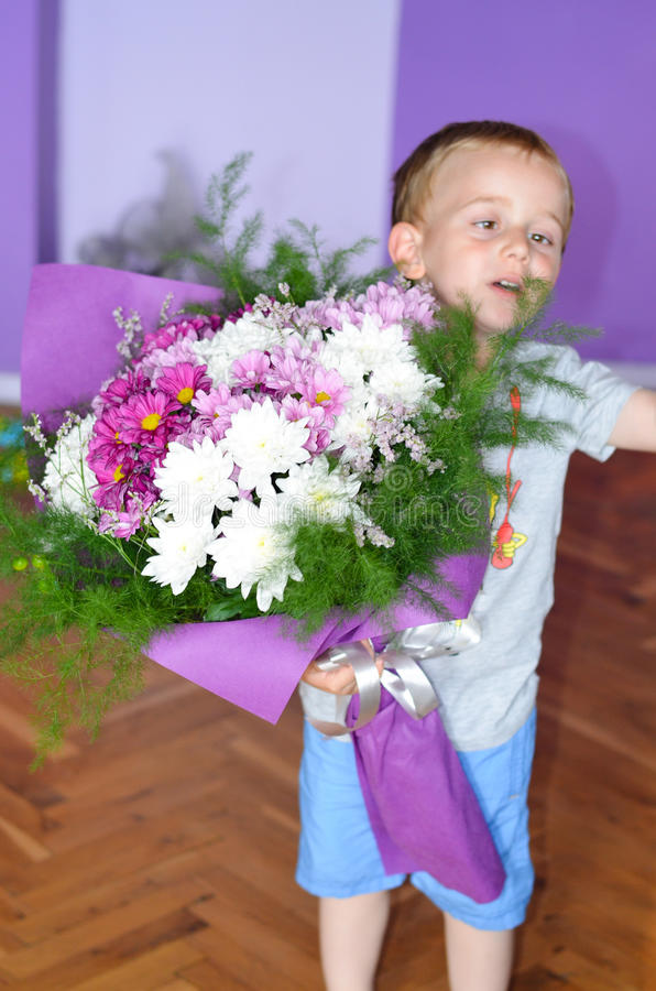 Little cute boy giving flowers stock image
