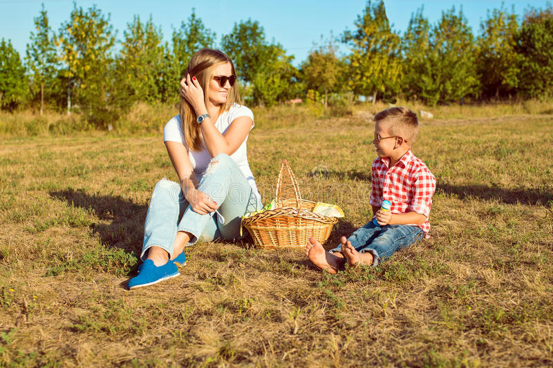 Little cute boy is having picnic with his young beautiful mother stock image