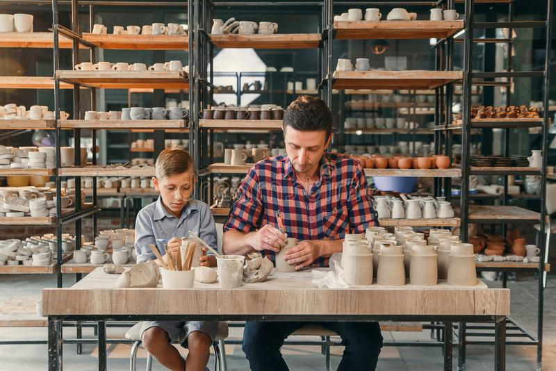 Little cute boy with his father making ceramic pots in the pottery. royalty free stock photos