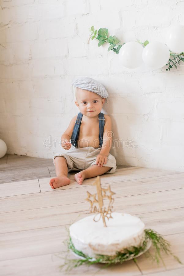 Little cute boy on his first birthday with a festive cake and decor with white balloons and sprigs of eucalyptus. Rustic First Birthday Party royalty free stock photography