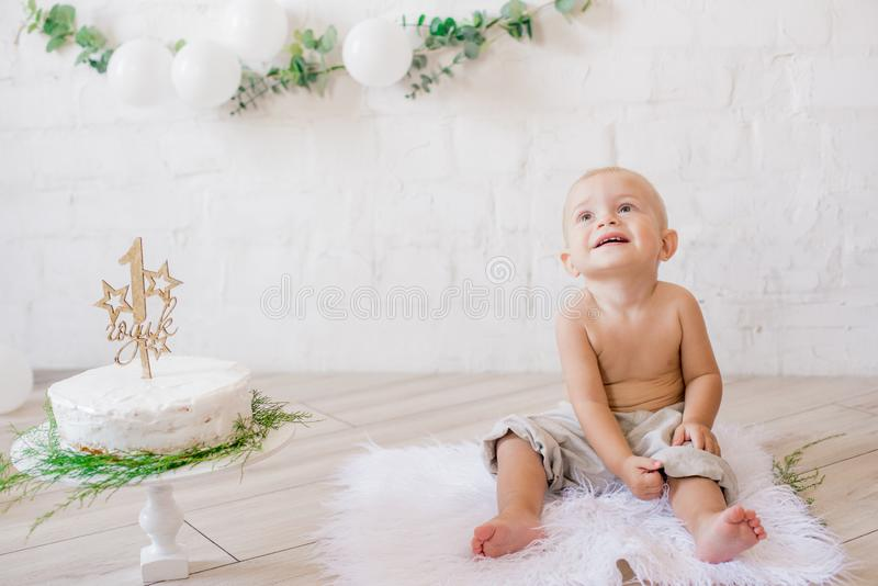 Little cute boy on his first birthday with a festive cake and decor with white balloons and sprigs of eucalyptus. Rustic First Birthday Party royalty free stock image