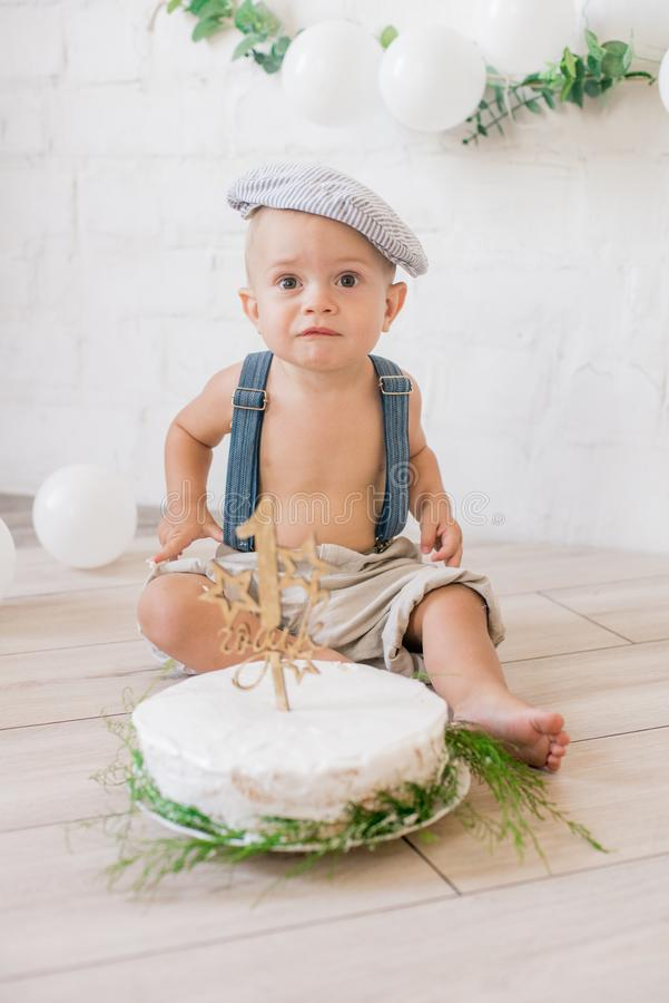 Little cute boy on his first birthday with a festive cake and decor with white balloons and sprigs of eucalyptus. Rustic First Birthday Party stock photos
