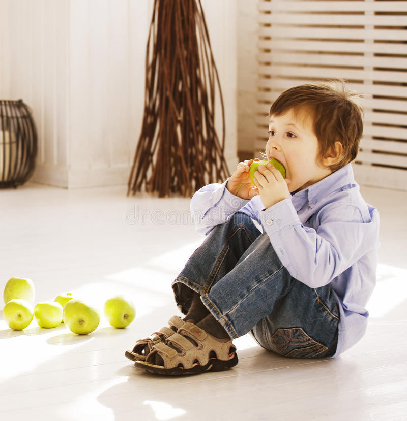 Little cute boy at home eating green apple stock photos