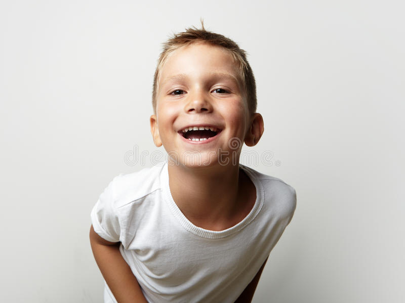 Little cute boy laughing at the camera. Blank wall royalty free stock image