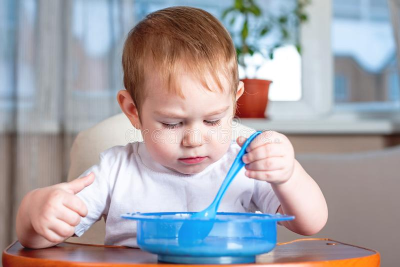 Little cute boy learning to eat with a spoon himself in the kitchen. Concept of healthy baby food. Little baby boy learning to eat with a spoon himself at the stock photo