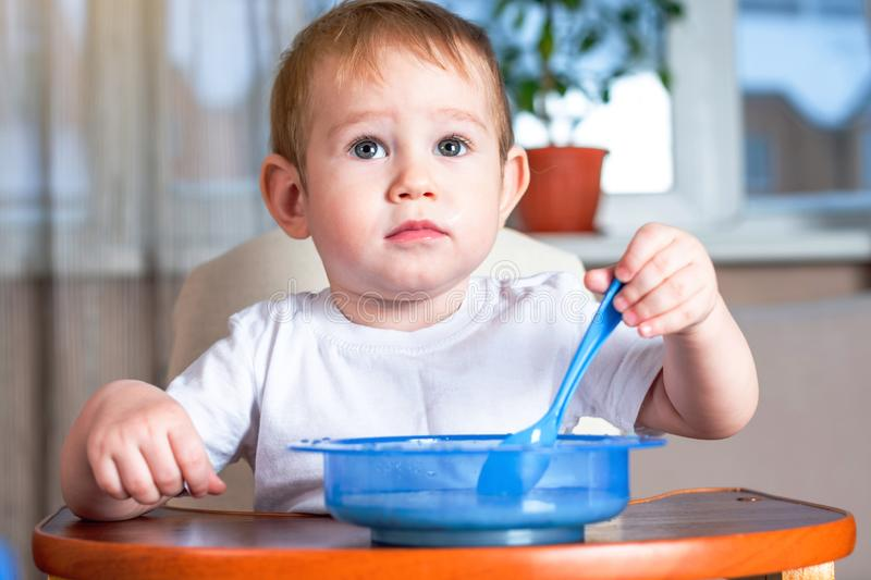 Little cute boy learning to eat with a spoon himself in the kitchen. Concept of healthy baby food. Little baby boy learning to eat with a spoon himself at the royalty free stock photography