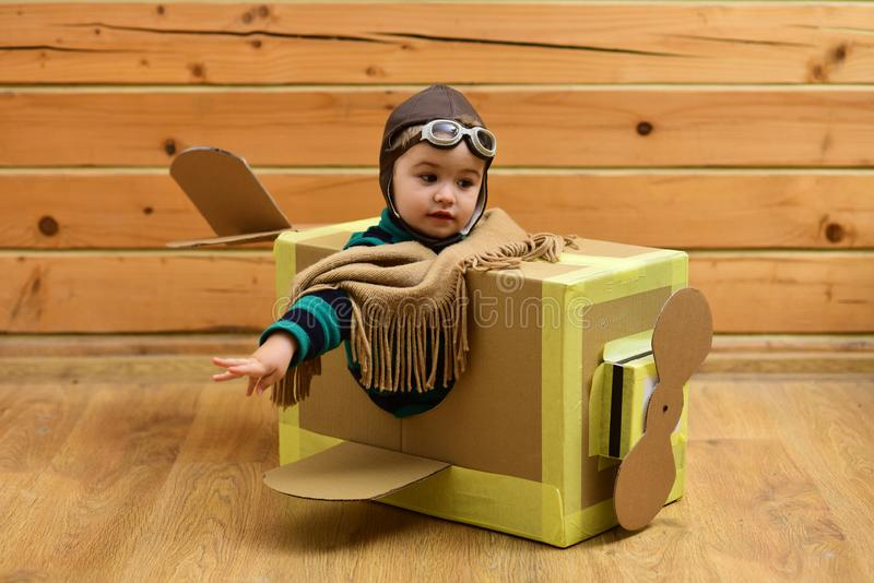 Little cute boy playing with a cardboard airplane. stock photography