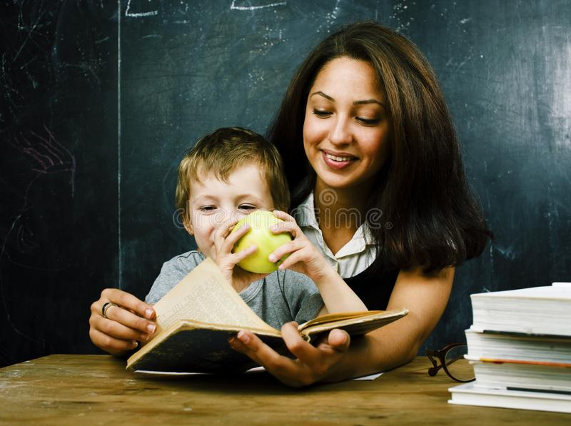 little cute boy pupil with young real teacher, classroom studyin royalty free stock images