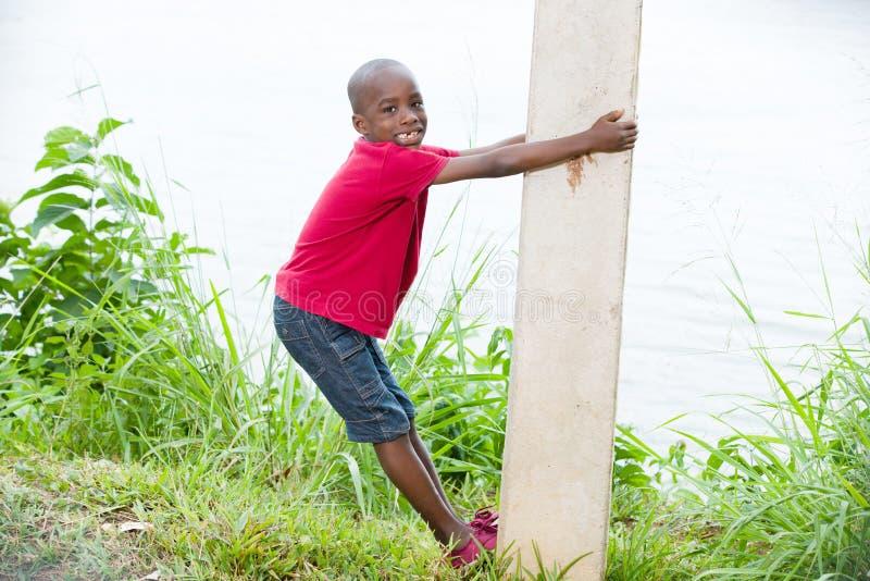 Portrait of a little boy climbing a pole royalty free stock photo
