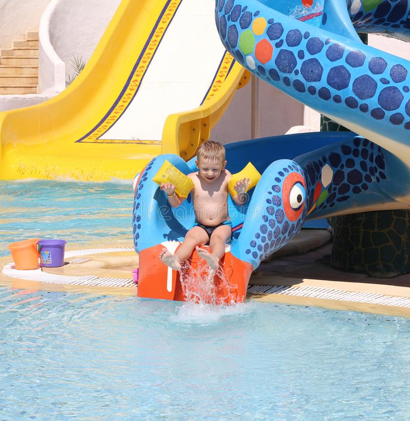 Little cute boy rolls down from the water slide into the pool. Water park for children. Happy boy on vacation. Holidays at sea with children stock image