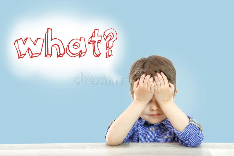 Little cute boy sits and asks what on an isolated background royalty free stock photo