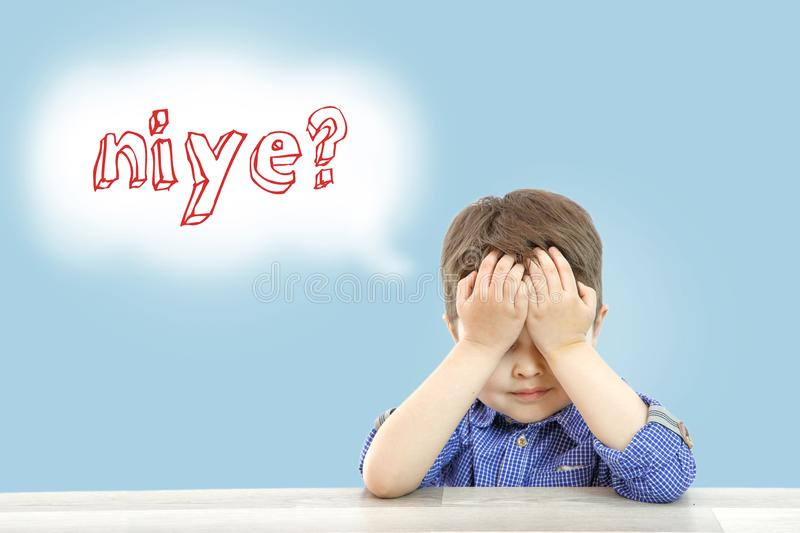 Little cute boy sits and asks why in Turkish language on an isolated background royalty free stock photo