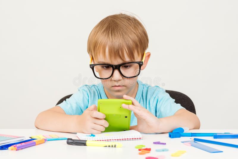 Little cute boy sits at table and counts something with calculator. Kid study and learn. Child doing homework at home. Little royalty free stock images