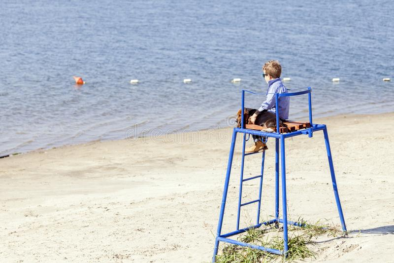 Little cute boy is sitting at the watchtower on the beach with stock image
