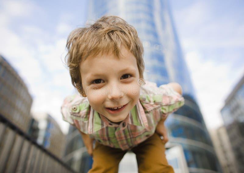 Little cute boy standing near business building, smiling stock photos