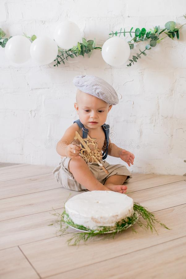 Little cute boy in suspenders and vintage cap. First birthday with a birthday cake and decor with white balloons. And sprigs of eucalyptus. Rustic First stock photography