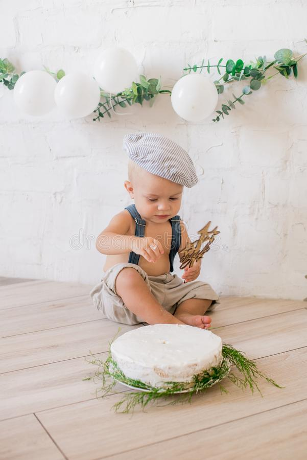 Little cute boy in suspenders and vintage cap. First birthday with a birthday cake and decor with white balloons. And sprigs of eucalyptus. Rustic First royalty free stock photography