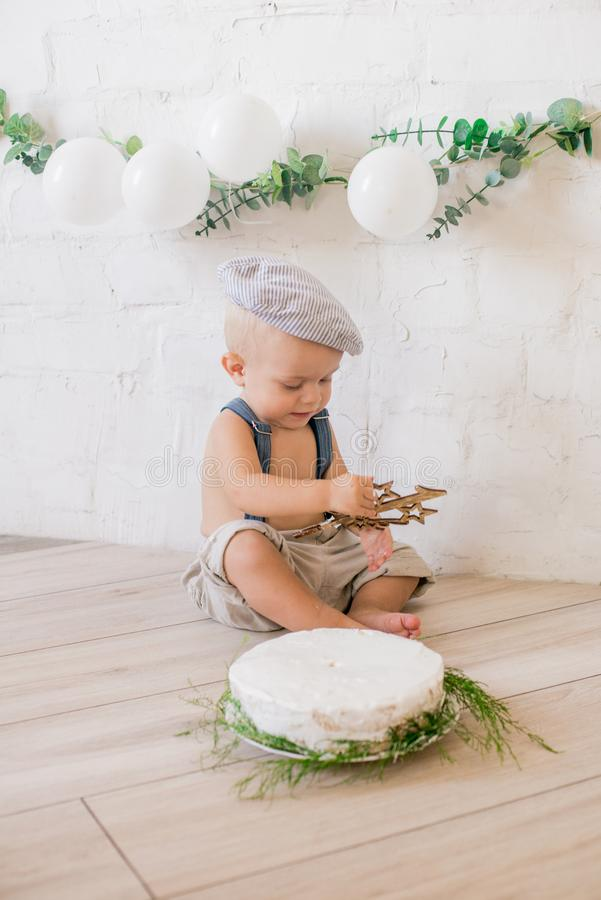 Little cute boy in suspenders and vintage cap. First birthday with a birthday cake and decor with white balloons. And sprigs of eucalyptus. Rustic First royalty free stock image