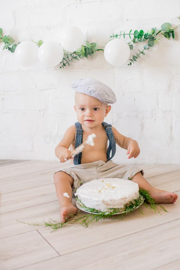 Little cute boy in suspenders and vintage cap. First birthday with a birthday cake and decor with white balloons. And sprigs of eucalyptus. Rustic First royalty free stock photos