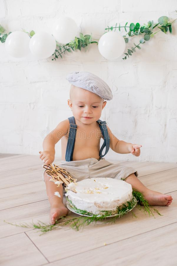 Little cute boy in suspenders and vintage cap. First birthday with a birthday cake and decor with white balloons. And sprigs of eucalyptus. Rustic First stock image
