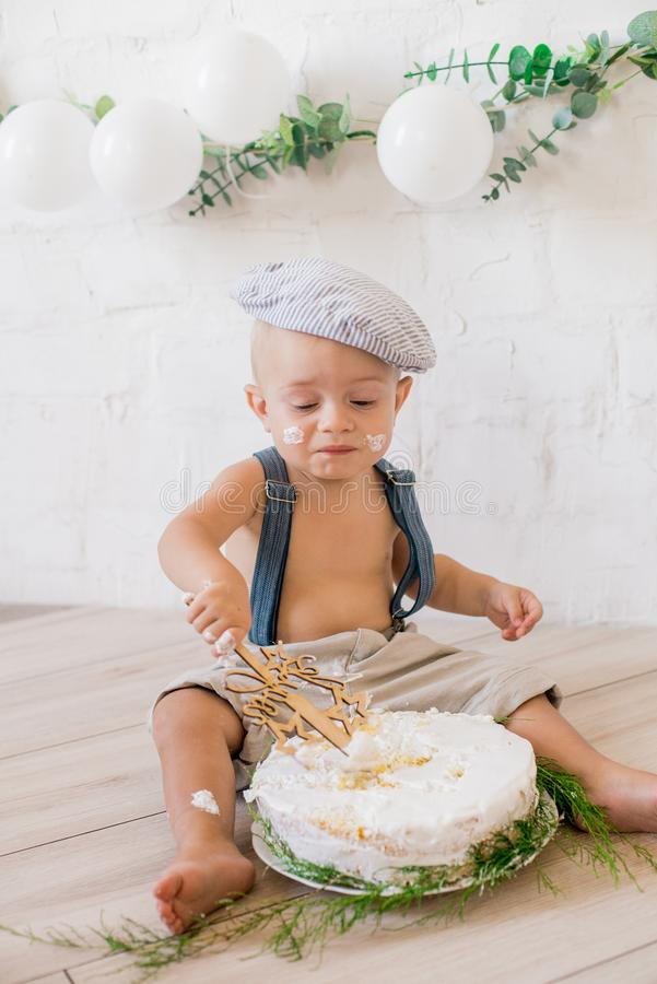 Little cute boy in suspenders and vintage cap. First birthday with a birthday cake and decor with white balloons. And sprigs of eucalyptus. Rustic First royalty free stock photo