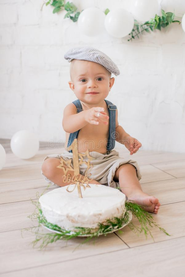 Little cute boy in suspenders and vintage cap. First birthday with a birthday cake and decor with white balloons. And sprigs of eucalyptus. Rustic First stock photos