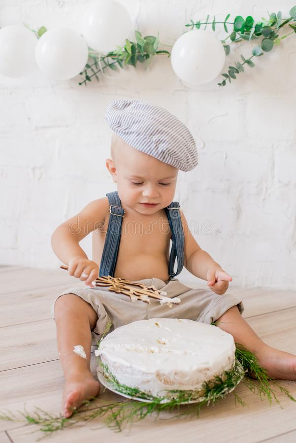 Little cute boy in suspenders and vintage cap. First birthday with a birthday cake and decor with white balloons. And sprigs of eucalyptus. Rustic First royalty free stock images