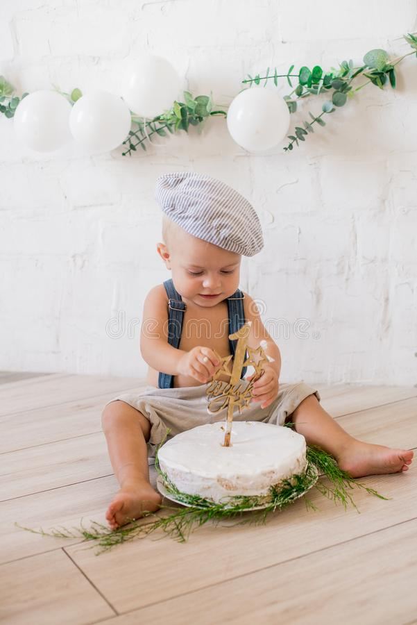 Little cute boy in suspenders and vintage cap. First birthday with a birthday cake and decor with white balloons. And sprigs of eucalyptus. Rustic First stock images