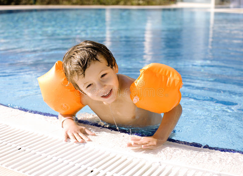 Little cute boy in swimming pool wearing. Orange handcarves stock photography