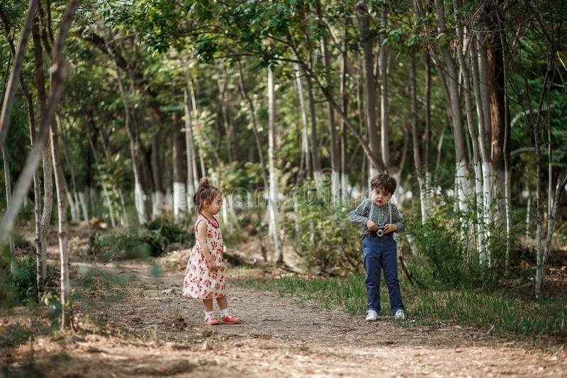 A little cute boy in vintage clothes and a little beautiful girl in a retro dress are walking in the woods and taking pictures. stock images