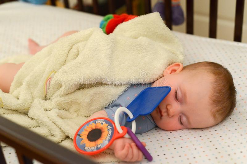 Little cute Caucasian baby is sleeping in the crib. Infant holds toy. royalty free stock photos