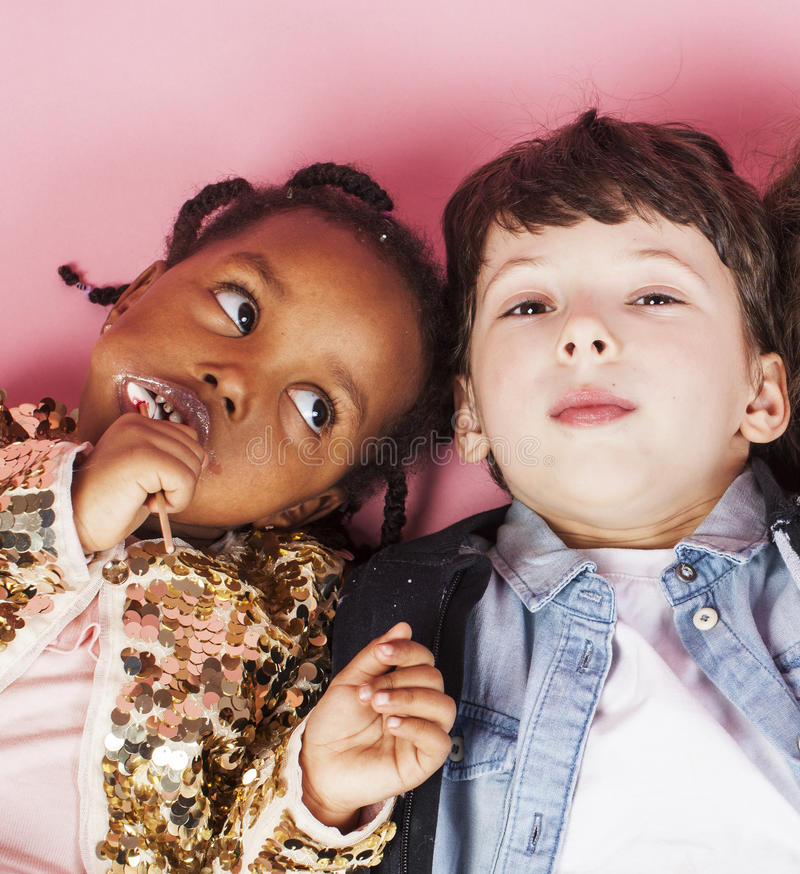 Little cute caucasian boy and african american girl hugging playing on pink background, happy smiling diverse nation and royalty free stock images