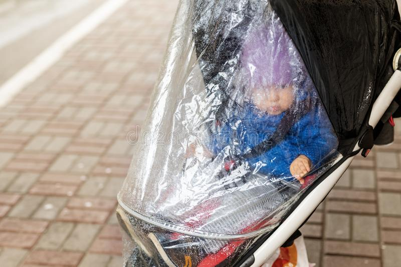 Little cute caucasian toddler boy in casual sport clothes having fun enjoy walking during rain in autumn day. Child. Sitting in stroller with rain protection royalty free stock images