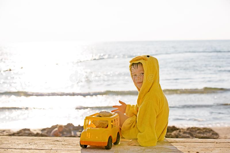 Little cute child baby boy sitting at sea on sand beach, play with toy car truck. Little kid son playing outdoors. Love stock photos