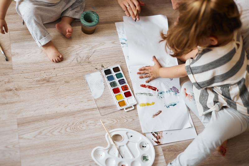Little cute child draws. finger paints, hand prints royalty free stock image