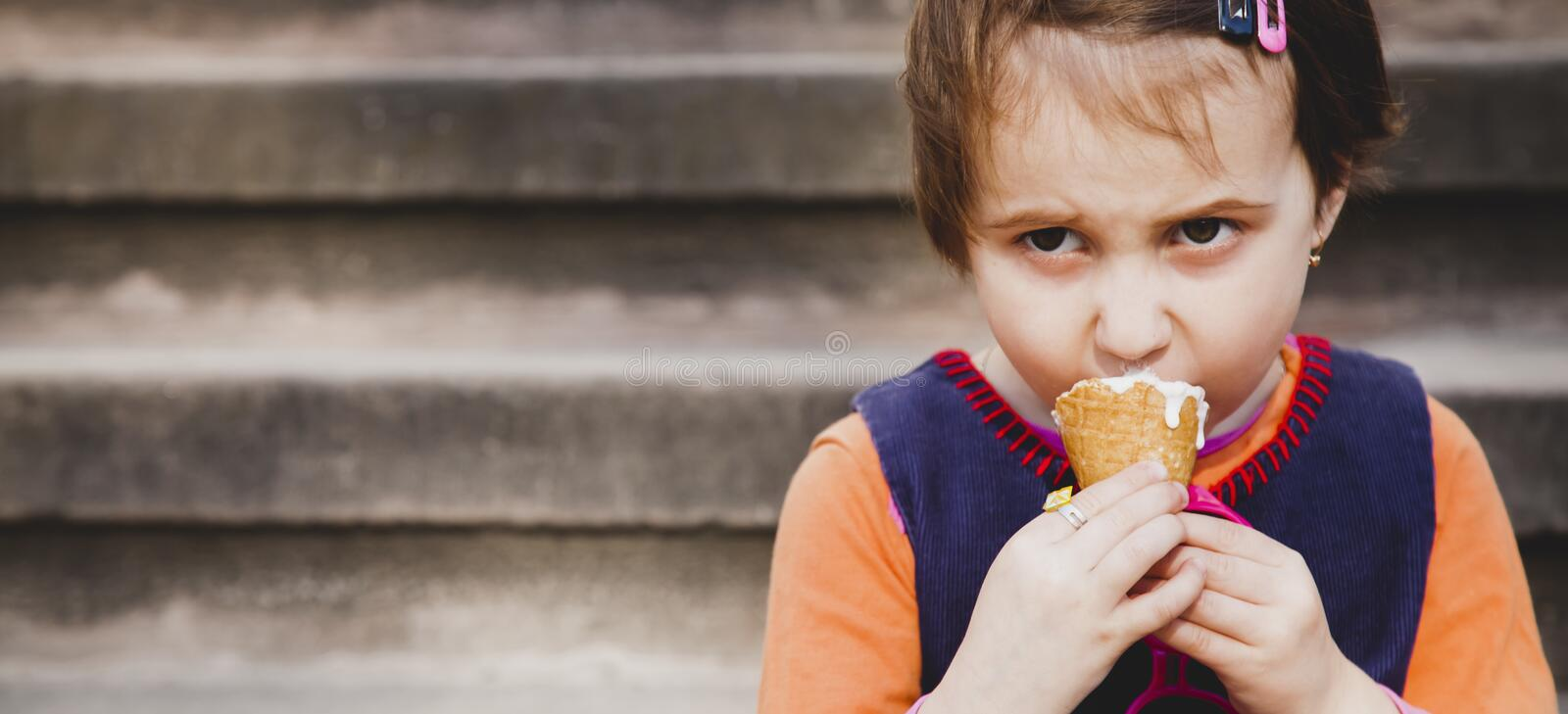 Little cute child girl eating ice cream. Food, dessert, childhood, satisfaction, carelessness concept.  royalty free stock photo