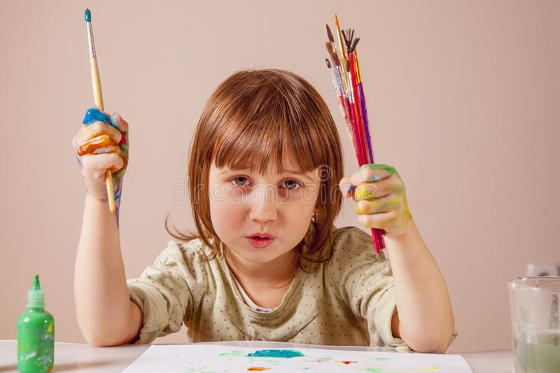 Little cute child girl painting with a brushes. Art, creativity, beauty childhood concept stock image