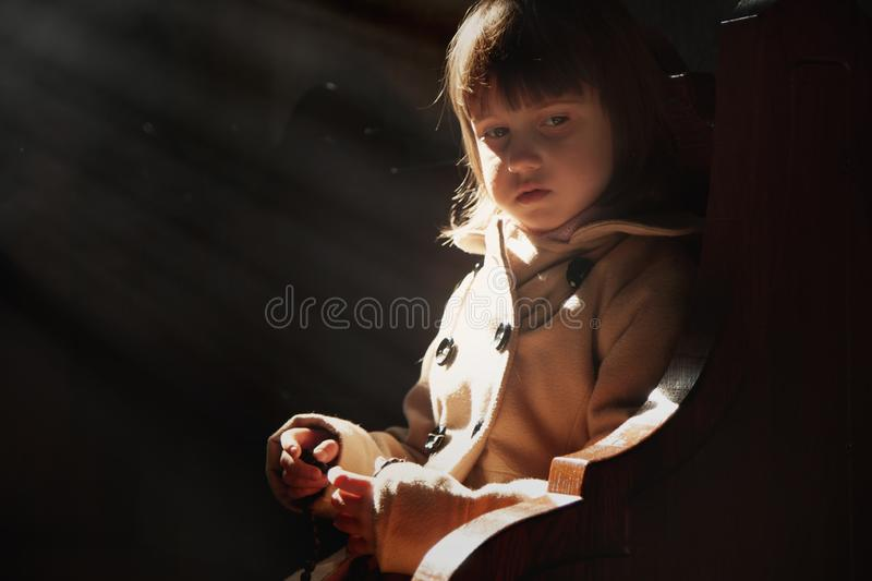 Little cute child girl praying in the church. Faith concept stock image