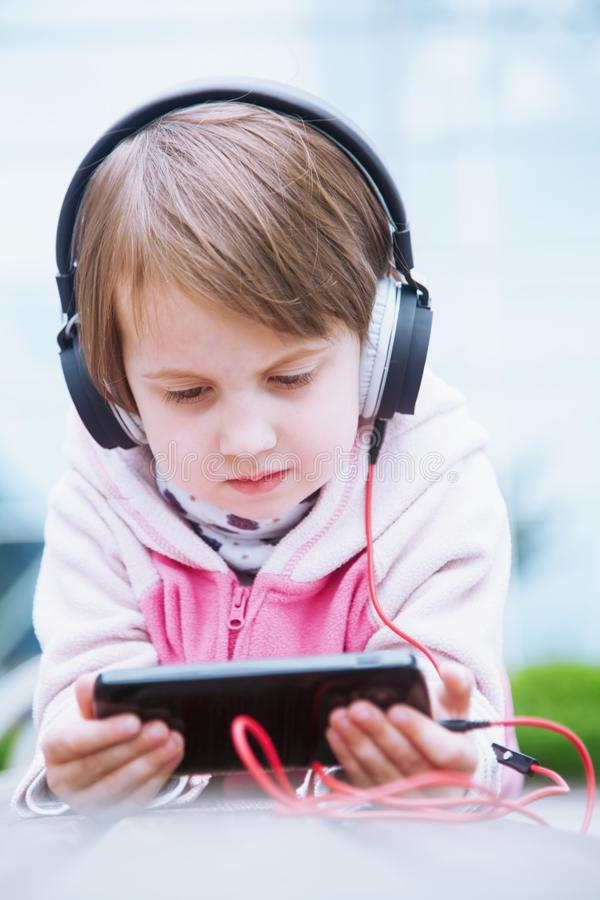 Little cute child girl wearing headphones listens online web free audio course outdoors, female kid using mobile phone for e- royalty free stock photo
