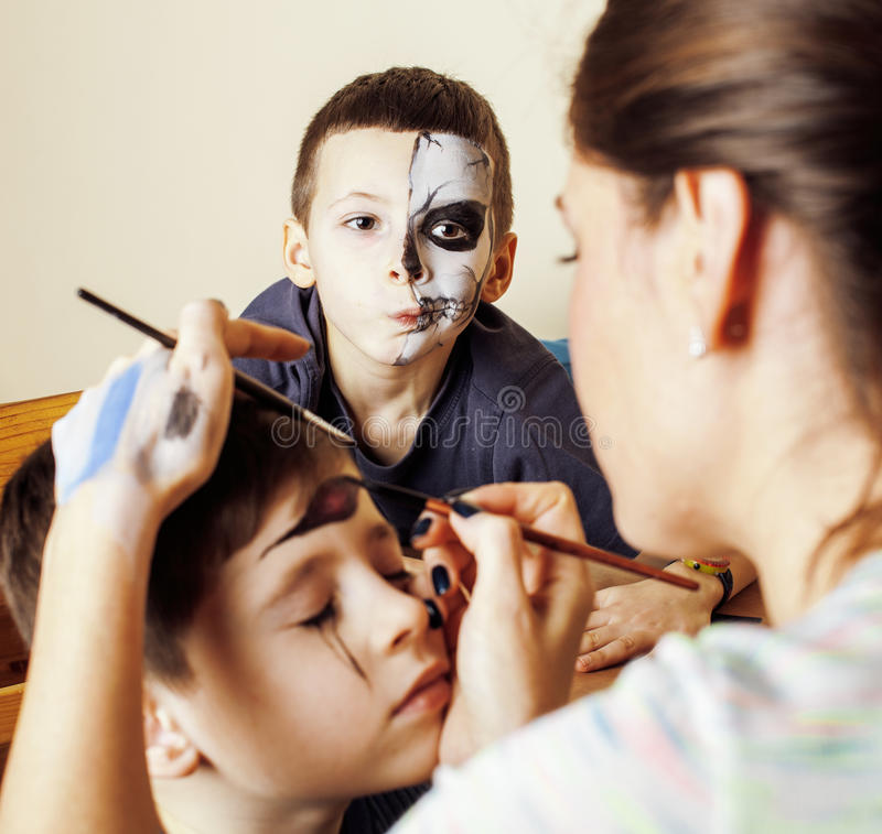 Little cute child making facepaint on birthday party, zombie Apocalypse facepainting, halloween preparing concept. Close up stock photos