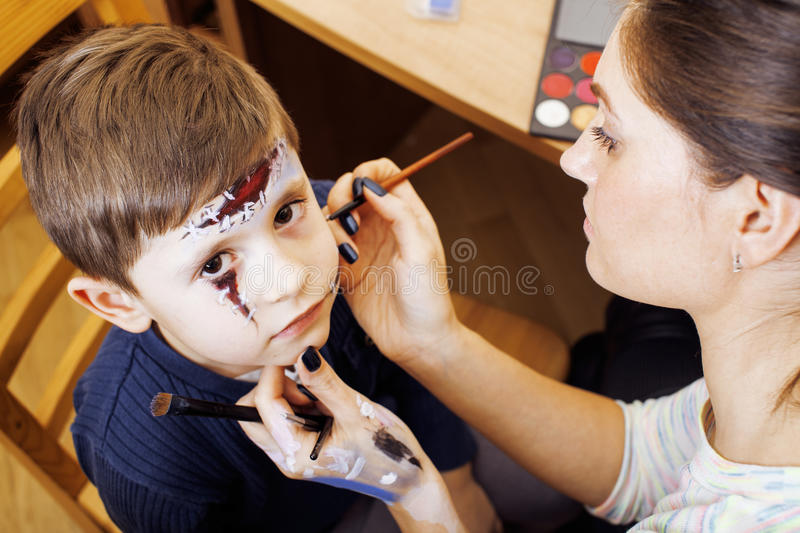 Little cute child making facepaint on birthday party, zombie Apocalypse facepainting, halloween preparing concept royalty free stock photography