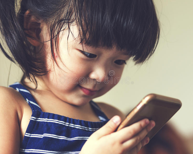A little cute child playing cell phone device royalty free stock photo
