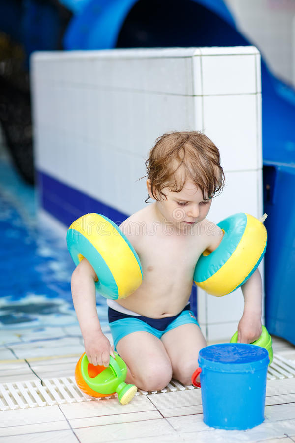 Little cute child playing and having fun in swimming pool royalty free stock photo