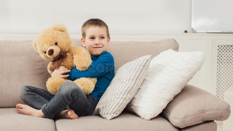 Little cute child with Teddy bear at living room. Little cute child playing with Teddy bear at living room having fun and happiness stock photo